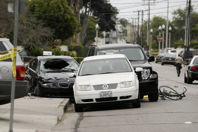 Police tap marks of the scene where a black BMW sedan, left, driven by a drive-by shooter, rests on Saturday, May 24, 2014, in Isla Vista, Calif.