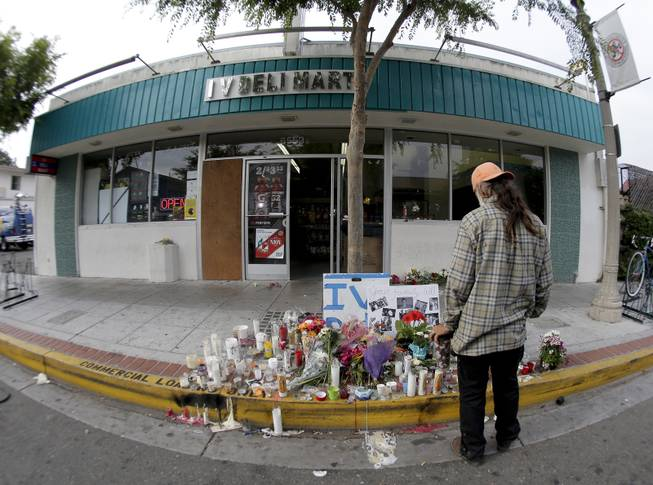 A passerby pays his respects at a makeshift memorial in front of the IV Deli Mart, Sunday, May 25, 2014, the scene of a drive-by shooting Friday in the Isla Vista area near Goleta, Calif.