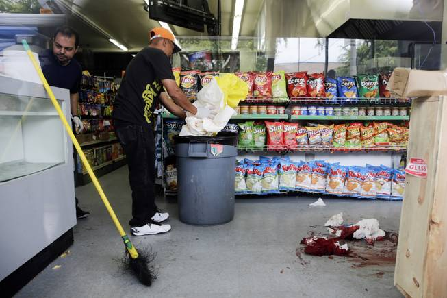 IV Deli Mart owner Michael Hassan, left, and his employee clean up the store where part of Friday night's mass shooting took place by a drive-by shooter, on Saturday, May 24, 2014, in Isla Vista, Calif.