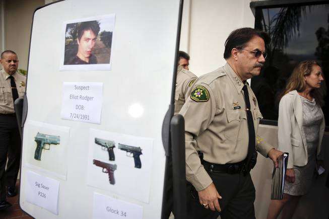 Santa Barbara County Sheriff Bill Brown, right, walks past a board showing the photos of suspected gunman Elliot Rodger and the weapons he used in Friday night's mass shooting that took place in Isla Vista, Calif., after a news conference on Saturday, May 24, 2014, in Santa Barbara, Calif.