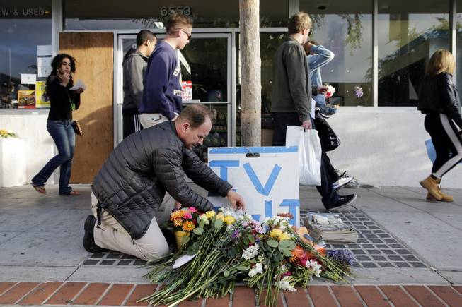 Stephen Nichols arranges flowers left in front of IV Deli Mart, where part of Friday night's mass shooting took place by a drive-by shooter, on Saturday, May 24, 2014, in Isla Vista, Calif.