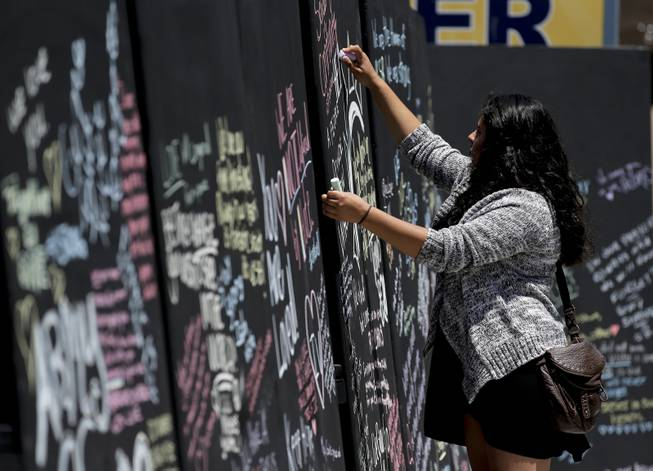Daniela Bayon writes on a remembrance wall across the street from the IV Deli Mart, where part of the mass killings took place, on Tuesday, May 27, 2014 in the Isla Vista area near Goleta, Calif.
