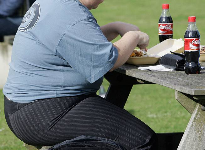 In this file photo dated Wednesday, Oct. 17, 2007, an overweight person eats in London. Almost one-third of the world population is now fat, and no country has been able to curb obesity rates in the last three decades, according to a new global analysis to be released Thursday, May 29, 2014.
