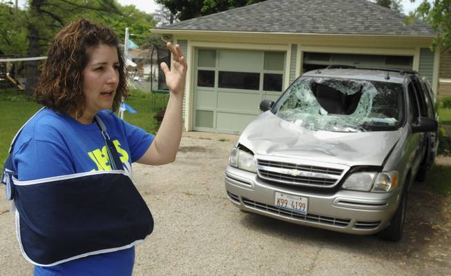 In this Tuesday, May 27, 2014, photo, Heidi Conner of West Dundee, Ill., describes how a 200-pound deer leaped from an overpass and landed on her minivan as her four children and she traveled along an Illinois interstate Sunday. Conner says the accident totaled the van and caused minor injuries.
