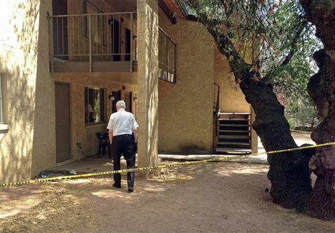 A police volunteer stands outside an apartment in Payson, Ariz., on Tuesday, May 27, 2014, after a 3-year-old boy shot and killed his 1½ -year-old brother, according to Police Chief Don Engler. According to authorities, the boys found a handgun in a neighbor's apartment and took it to another room where the shooting occurred.