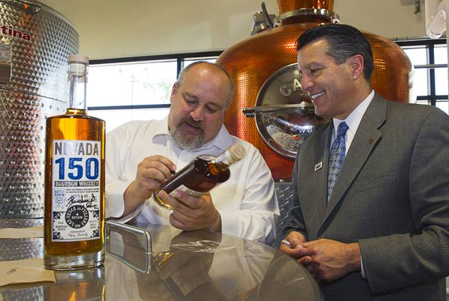 "Distillery owner George Racz, left, and Nevada Governor Brian Sandoval autograph bottles of ""Nevada 150"" bourbon at the Las Vegas Distillery in Henderson Thursday, May 29, 2014. Governor Sandoval helped fill the first bottle of ""Nevada 150,"" a bourbon whiskey created for the Nevada sesquicentennial."