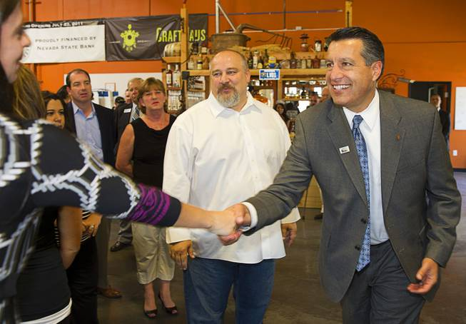 "Nevada Governor Brian Sandoval, right, greets guests as he arrives at the Las Vegas Distillery in Henderson Thursday, May 29, 2014. Distillery owner George Racz looks on at center. Governor Sandoval helped fill the first bottle of ""Nevada 150,"" a bourbon whiskey created for the Nevada sesquicentennial."