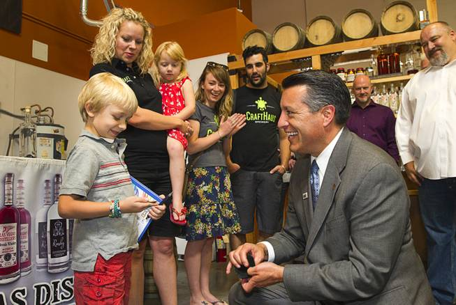"Brooks Forrest, 6, receives a ""Governor's coin"" from Nevada Governor Brian Sandoval at the Las Vegas Distillery in Henderson Thursday, May 29, 2014. Governor Sandoval helped fill the first bottle of ""Nevada 150,"" a bourbon whiskey created for the Nevada sesquicentennial."