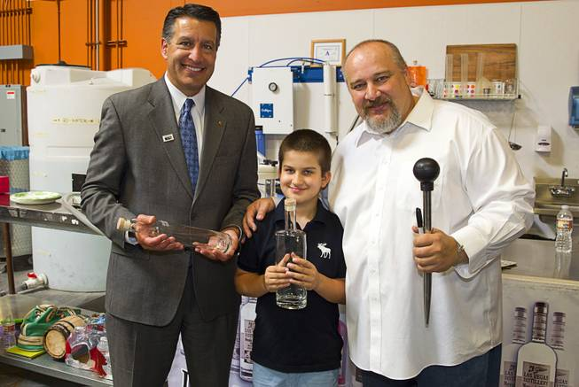 "Nevada Governor Brian Sandoval, left, poses with distillery owner George Racz and George Alexander Racz, 7, at the Las Vegas Distillery in Henderson Thursday, May 29, 2014. Governor Sandoval helped fill the first bottle of ""Nevada 150,"" a bourbon whiskey created for the Nevada sesquicentennial."