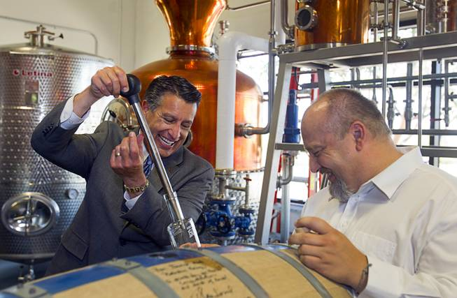 "Nevada Governor Brian Sandoval, left, and distillery owner George Racz fill a bottle with whiskey after breaking open the ""Governor's Barrel"" at the Las Vegas Distillery in Henderson Thursday, May 29, 2014. Governor Sandoval helped fill the first bottle of ""Nevada 150,"" a bourbon whiskey created for the Nevada sesquicentennial."
