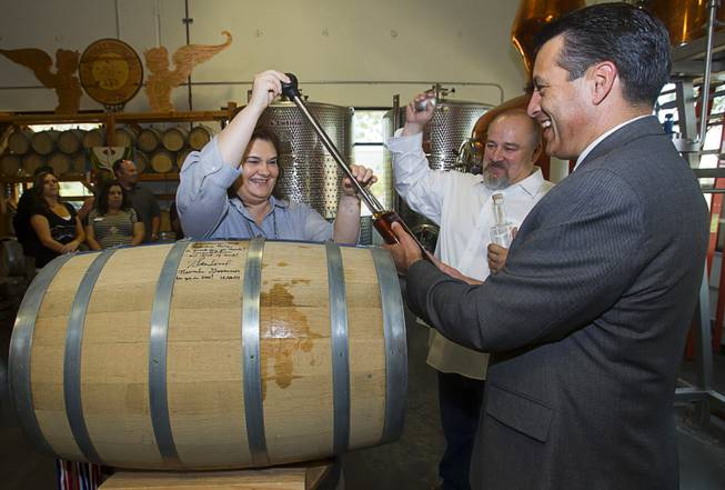 "Distillery owners Katalin and George Racz fill a bottle of whiskey with Nevada Governor Brian Sandoval at the Las Vegas Distillery in Henderson Thursday, May 29, 2014. Governor Sandoval helped fill the first bottle of ""Nevada 150,"" a bourbon whiskey created for the Nevada sesquicentennial."