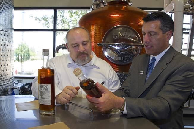 "Nevada Governor Brian Sandoval, right, looks over a bottle of ""Nevada 150"" bourbon with distillery owner George Racz at the Las Vegas Distillery in Henderson Thursday, May 29, 2014. Governor Sandoval helped fill the first bottle of ""Nevada 150,"" a bourbon whiskey created for the Nevada sesquicentennial."