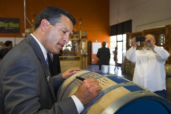 "Nevada Governor Brian Sandoval signs the ""Governor's Barrel"" as distillery owner George Racz takes a photo at the Las Vegas Distillery in Henderson Thursday, May 29, 2014. Governor Sandoval helped fill the first bottle of ""Nevada 150,"" a bourbon whiskey created for the Nevada sesquicentennial."