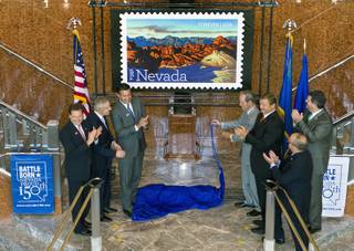 Invited dignitaries unveil the Nevada Sesquicentennial commemorative stamp as part of a United States Postal Service and Nevada Sesquicentennial Commission event at the Smith Center on Thursday, May 29, 2014.