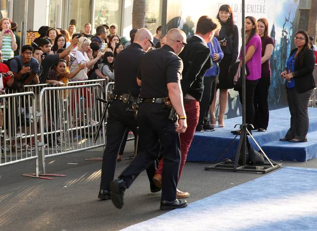 "Journalist Vitalii Sediuk is walked off the carpet in handcuffs after allegedly attacking Brad Pitt at the world premiere of ""Maleficent"" at the El Capitan Theater on Wednesday, May 28, 2014, in Los Angeles."