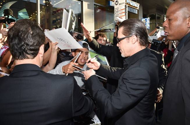 "Brad Pitt signs autographs at the world premiere of ""Maleficent"" at the El Capitan Theatre on Wednesday, May 28, 2014, in Los Angeles."