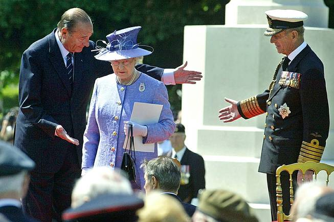 In this June 6, 2004, file photo, French President Jacques Chirac, left, greets Queen Elizabeth II, of Britain, and her husband Prince Philip at the British military cemetery in Bayeux, northwestern France, during ceremonies marking the 60th anniversary of the D-Day landings in Normandy.