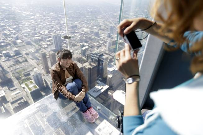 A tourist is photographed on the floor of one of four transparent ledges that jut out from the 103rd floor of the Willis Tower in Chicago on Thursday, May 29, 2014.