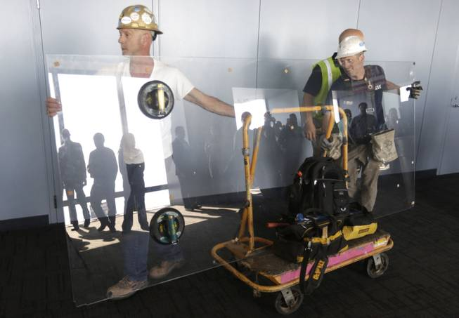 Glaziers from MTH Industries arrive to replace a layer of protective coating over the glass surface on the floor of one of four transparent ledges that jut out from the 103rd floor of the Willis Tower in Chicago on Thursday, May 29, 2014.