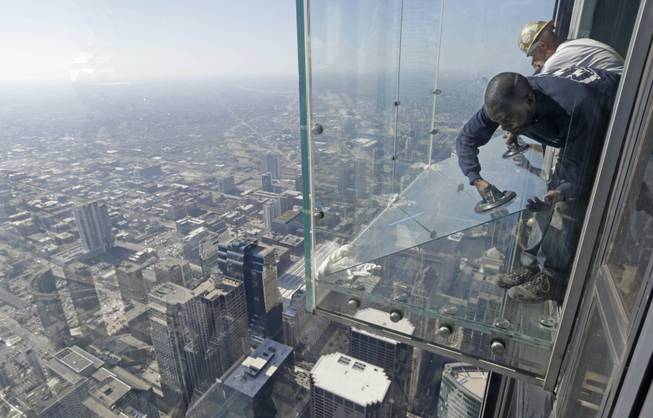 Glaziers from MTH Industries replace a layer of protective coating over the glass surface on the floor of one of four transparent ledges that jut out from the 103rd floor of the Willis Tower in Chicago on Thursday, May 29, 2014.