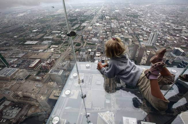 "This June 24, 2009 file photo shows Anna Kane, 5, looking down from the ""The Ledge,"" at Chicago's Willis Tower."