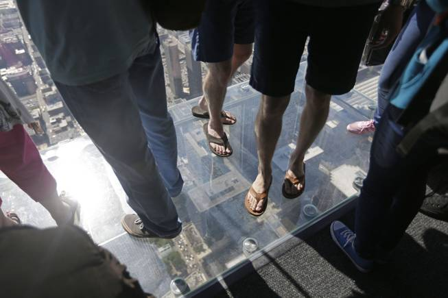 People stand on the floor of one of four transparent ledges that jut out from the 103rd floor of the Willis Tower in Chicago on Thursday, May 29, 2014.