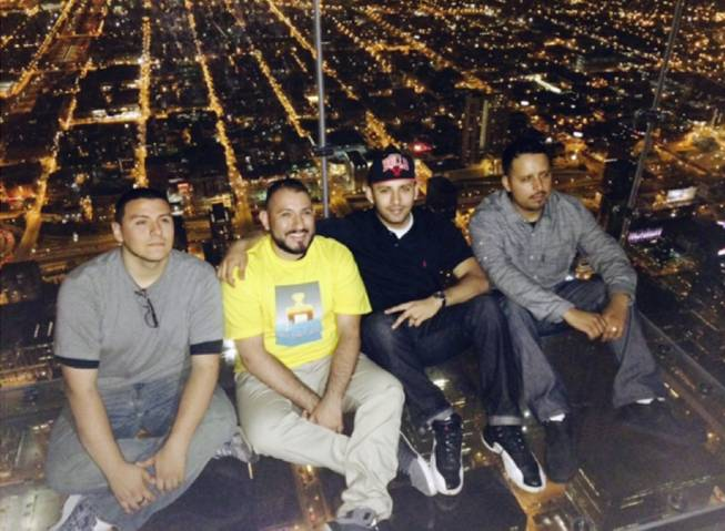 This Wednesday, May 28, 2014 photo provided by Alejandro Galibay shows Galibay, 23, of Stockton, Calif., second from right, sitting with his brother Ernesto, right, and cousins David Cazares, left, and Antonio Saldana on The Ledge, a popular tourist attraction on the 103rd floor of the Willis Tower in Chicago shortly before the coating protecting the glass bay they were sitting on started to crack. Garibay said Thursday, May 29, he knows now he wasn't in danger but when he first heard what sounded like breaking ice, he thought he was going to die.
