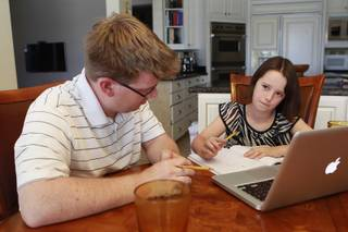 Ciara Swenson ponders a math problem with tutor Michael Christenson during a tutoring session in the Swenson's home Saturday, May 31, 2014.
