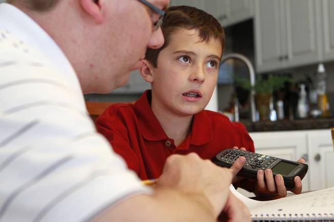 Aidan Swenson thinks about a math problem Michael Christenson during a tutoring session in the Swenson's home Saturday, May 31, 2014.