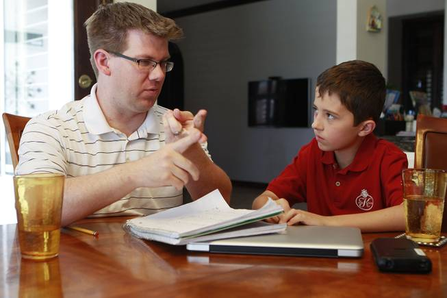 Tutor Michael Christenson explains a math problem to Aidan Swenson during a tutoring session in the Swenson's home Saturday, May 31, 2014.