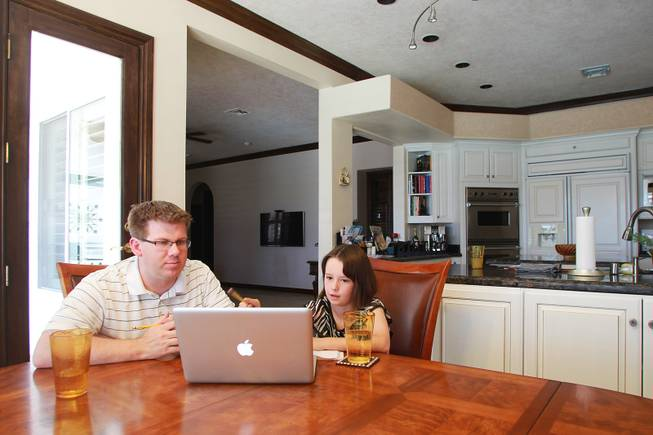Ciara Swenson and tutor Michael Christenson use an online math program during a tutoring session in the Swenson's home Saturday, May 31, 2014.