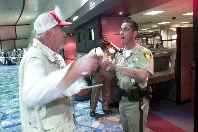 A man trying to locate his wife is denied passage to the gate area by Metro Police officer Frank Mandracchio at McCarran International Airport Tuesday, Sept. 11, 2001.