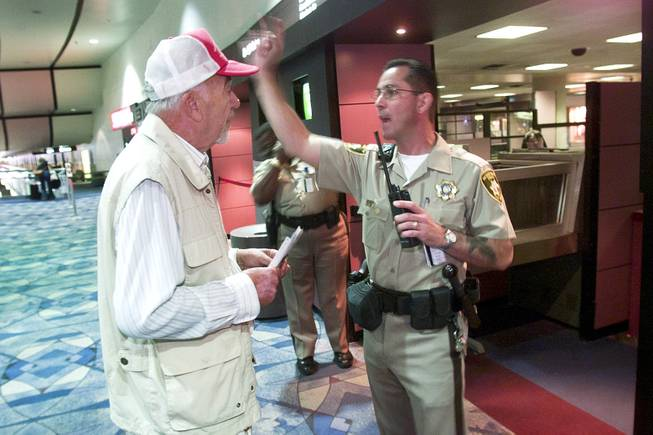 A man trying to locate his wife is denied passage to the gate area by Metro officer Frank Mandracchio at McCarran International Airport Tuesday, Sept. 11, 2001.