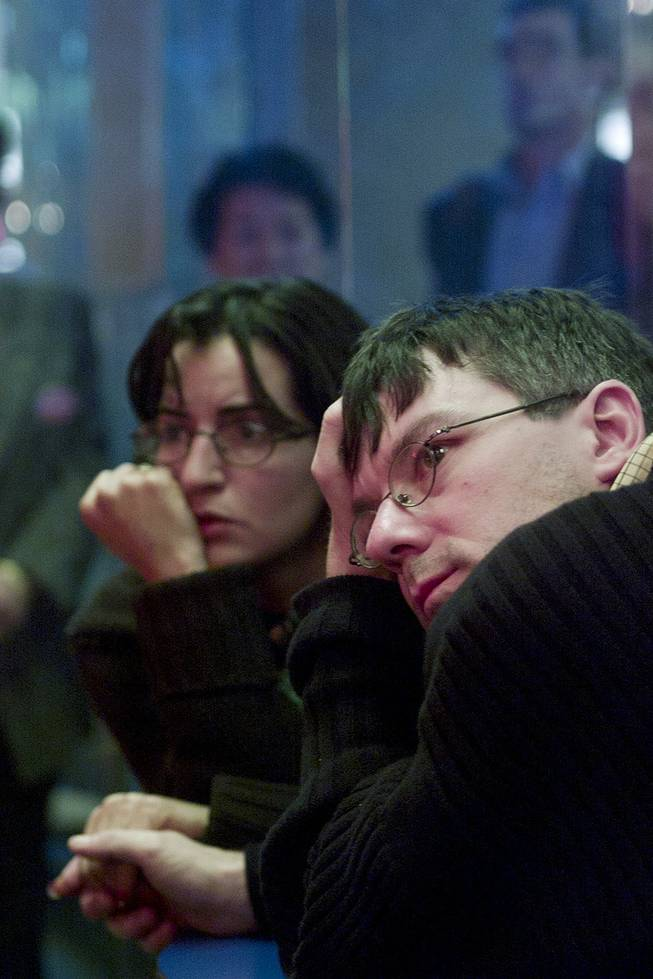French tourists watch coverage of terrorist attacks on televisions in a bar at McCarran International Airport Tuesday, Sept. 11, 2001.