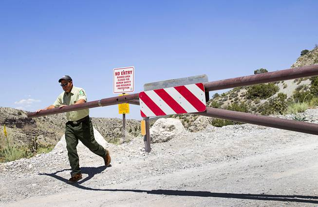Ron Bollier, a USFS fire management officer, opens a gate on Harris Springs Road on Mt. Charleston Tuesday, May 27, 2014. The road is temporarily closed to the public to give burned areas a chance to recover.