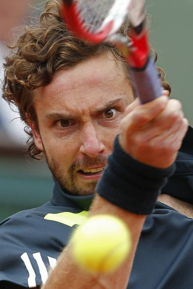 Latvia's Ernests Gulbis returns the ball during the fourth round match of the French Open tennis tournament against Switzerland's Roger Federer at the Roland Garros stadium, in Paris, France, Sunday, June 1, 2014. Gulbis won in five sets 6-7, 7-6, 6-2, 4-6, 6-3.
