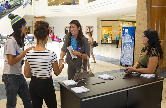 Lucy Flores, Democratic candidate for Lieutenant Governor, chats with shoppers after voting early at the Meadows Mall Monday, June 2, 2014. From left are: Brenda Osorio, Salvador Sanchez and Silvia Saenz. Early voting for the 2014 primary election continues through Friday June 6 at 83 sites.
