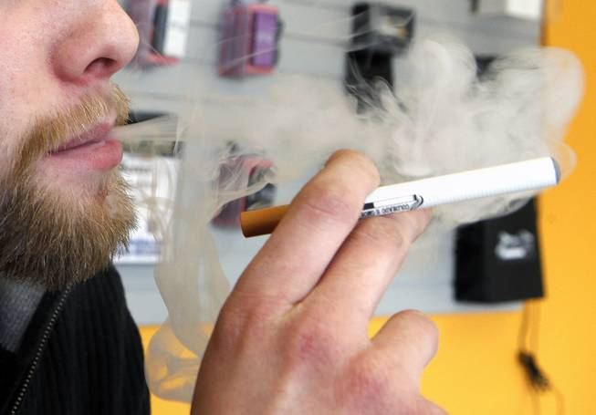 A sales associate demonstrates the use of a electronic cigarette and the smoke like vapor that comes from it in Aurora, Colo. on Wednesday, March 2, 2011.