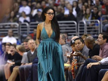 In this photo taken on Friday, Oct. 25, 2013, V. Stiviano, left, walks to her seat as she watches the Clippers play the Sacramento Kings during the first half of an NBA basketball game in Los Angeles.