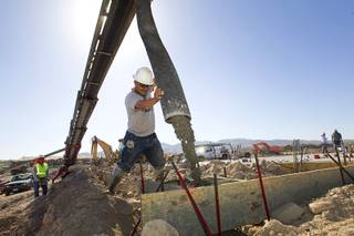 Francisco Bernal pours piers for patio columns while working on a KB Homes project at Inspirada in Henderson Tuesday, June 3, 2014. A number of formerly stalled or financially troubled master-planned communities are now back in business, with developers building and selling homes.