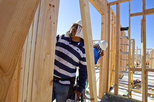 Carpenters work on a KB Homes project at Inspirada in Henderson Tuesday, June 3, 2014. A number of formerly stalled or financially troubled master-planned communities are now back in business, with developers building and selling homes.