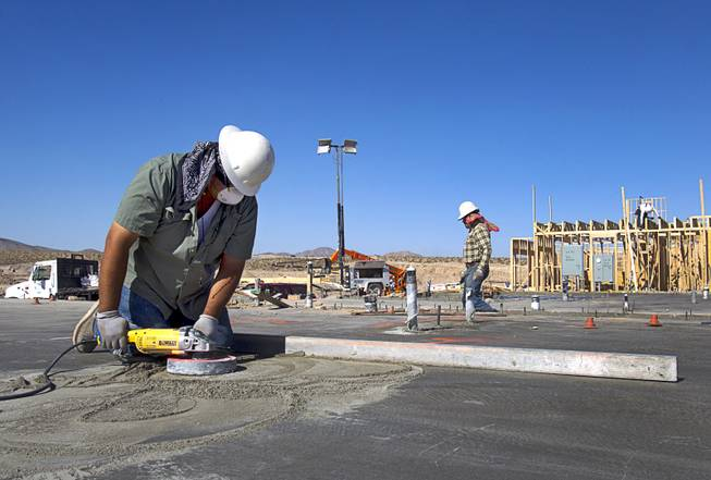 A worker grinds on a concrete slab at a KB Homes project at Inspirada in Henderson Tuesday, June 3, 2014. A number of formerly stalled or financially troubled master-planned communities are now back in business, with developers building and selling homes.