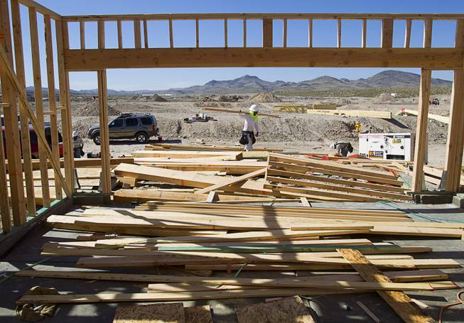 Workers frame a house at a KB Homes project at Inspirada in Henderson Tuesday, June 3, 2014. A number of formerly stalled or financially troubled master-planned communities are now back in business, with developers building and selling homes.