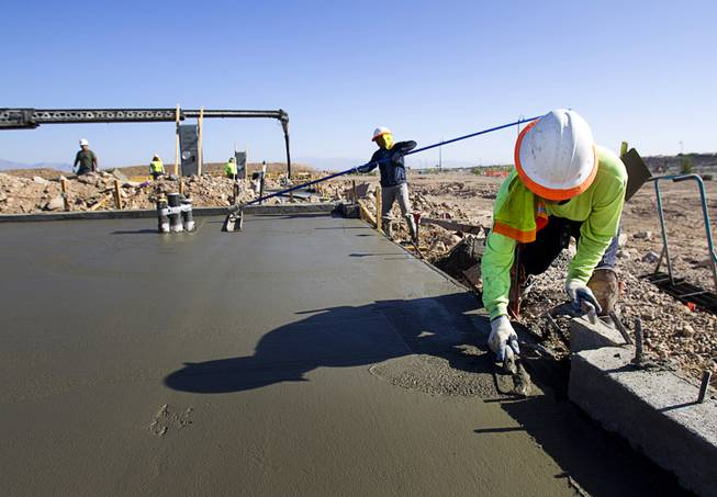 Workers finish a slab at a KB Homes project at Inspirada in Henderson Tuesday, June 3, 2014. A number of formerly stalled or financially troubled master-planned communities are now back in business, with developers building and selling homes.