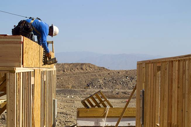 A carpenter works on a house at a KB Homes project at Inspirada in Henderson Tuesday, June 3, 2014. A number of formerly stalled or financially troubled master-planned communities are now back in business, with developers building and selling homes.