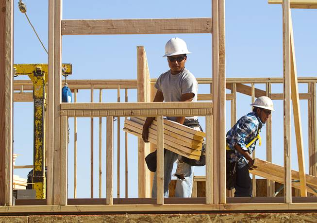 Carpenters frame a house at a KB Homes project at Inspirada in Henderson Tuesday, June 3, 2014. A number of formerly stalled or financially troubled master-planned communities are now back in business, with developers building and selling homes.