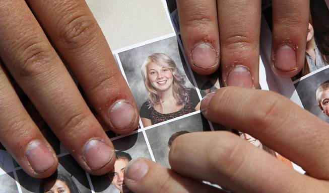 In this May 29, 2014, file photo, Wasatch High School sophomore Rachel Russell, 16, points to her altered school yearbook photo, center, in Heber City, Utah. Russell is one of several students at the school whose yearbook photos were digitally altered, with sleeves and higher necklines drawn on to cover up bare skin.