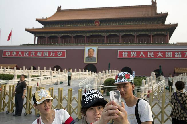 A Chinese woman takes a selfie on her mobile phone in front of Tiananmen Gate in Beijing Wednesday, June 4, 2014. Authorities in Beijing blanketed the city center with heavy security Wednesday on the 25th anniversary of the bloody military suppression of pro-democracy protests centered on Tiananmen Square.
