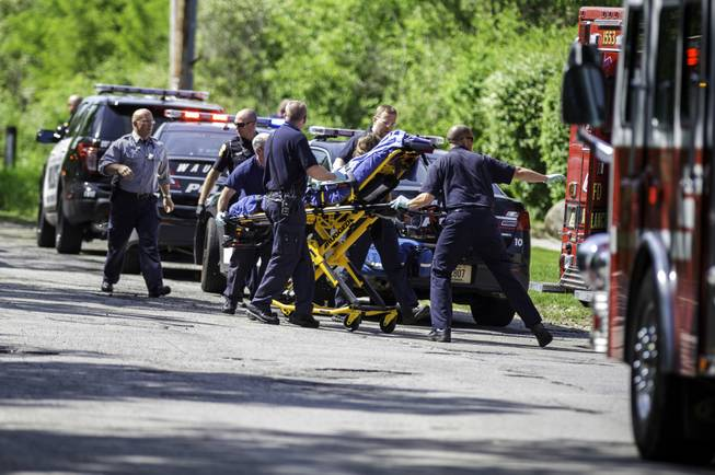 In this Saturday, May 31, 2014, photo, rescue workers take a stabbing victim to the ambulance in Waukesha, Wis. Prosecutors say two 12-year-old southeastern Wisconsin girls stabbed their 12-year-old friend nearly to death in the woods to please a mythological creature they learned about online.