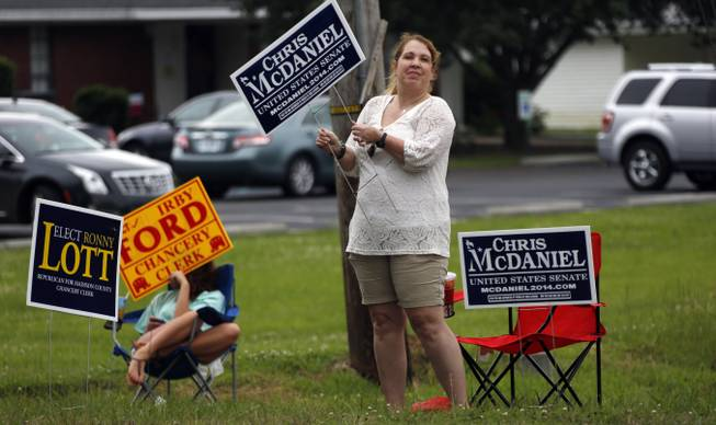 Lisa Bailey aggressively waves her campaign sign for state Sen. Chris McDaniel, who is running against incumbent U.S. Sen. Thad Cochran in the GOP primary, while Shelby Ford, 15, takes a more laid back approach to sidewalk campaigning for her father running for county chancery clerk by sitting in a lawn chair and waving his sign during the state's primary election, Tuesday, June 3, 2014, in Madison, Miss.